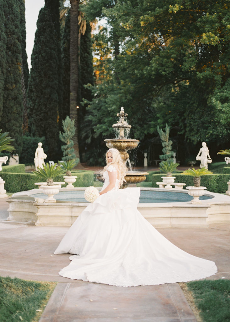 a bride twirls in front of the fountains at her Grand Island Mansion wedding