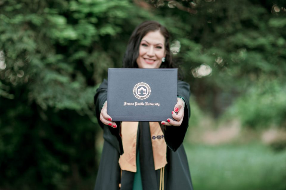 a woman shows off her diploma during grad photos