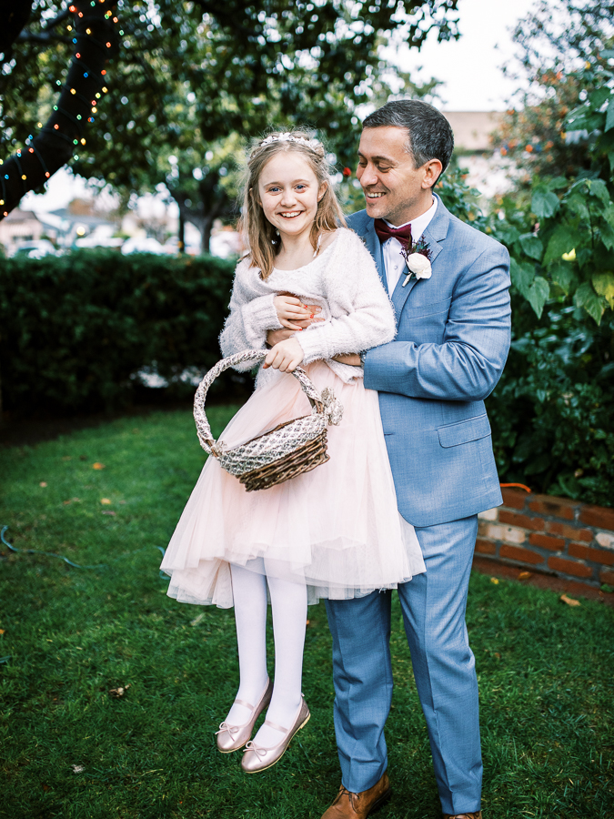 a groom plays with a flower girl before his Bay Area intimate wedding