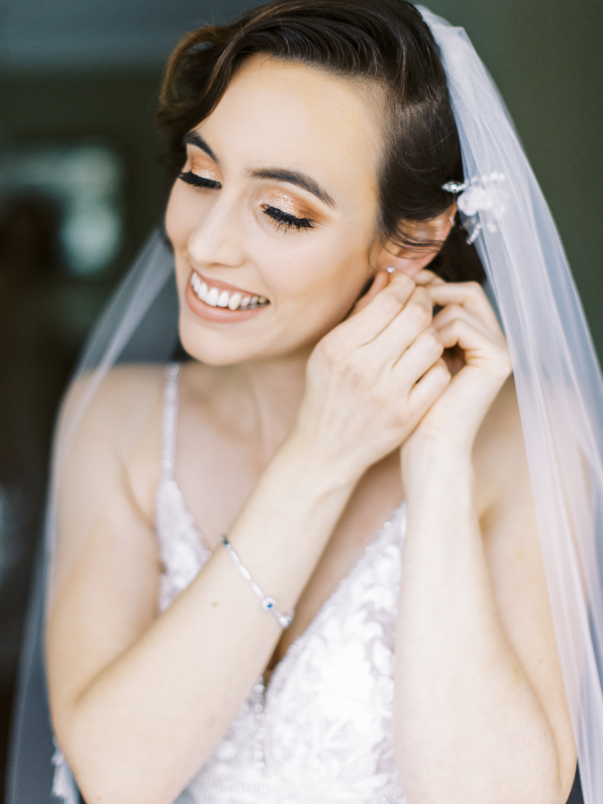 a bride puts on her earrings before her Bay Area intimate wedding