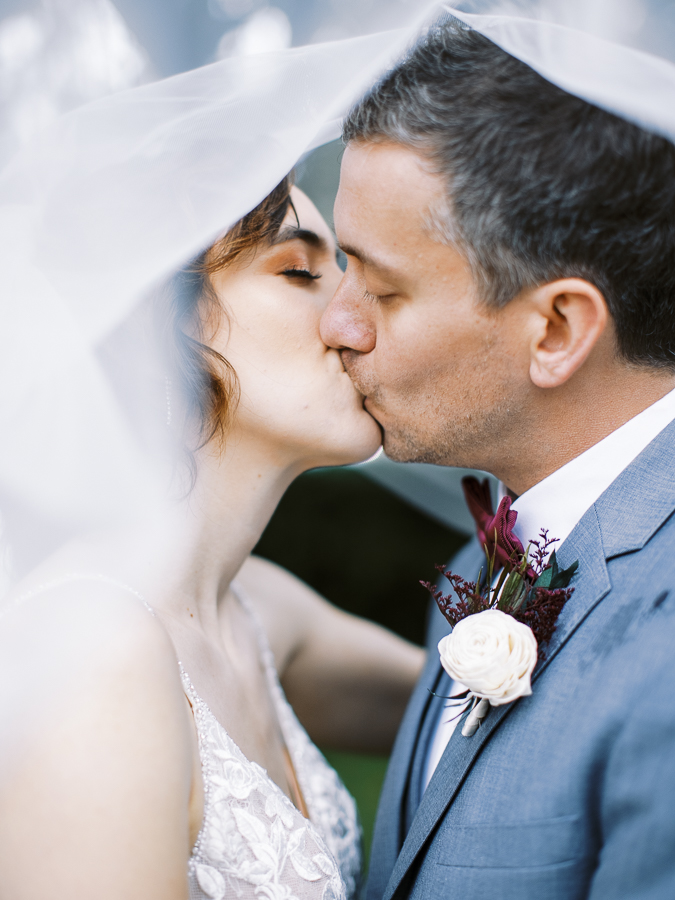 a bride and groom kiss beneath a veil during a Bay Area intimate wedding