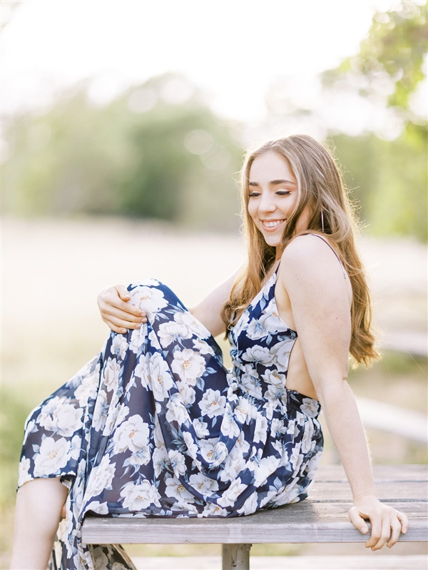 a senior laughs on a picnic table for how to prepare for senior photos