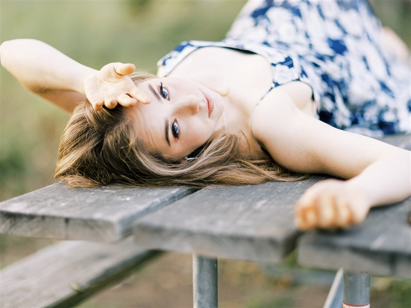 a senior lays for a pose on a picnic table to demonstrate one of her how to prepare for senior photos