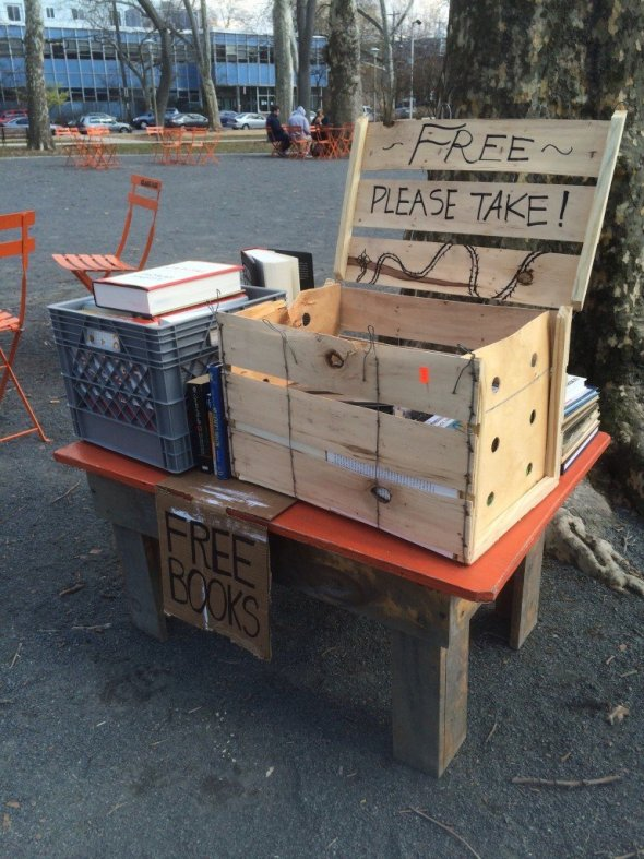 "Color photograph of two crates filled with books, a sign reading ""Free Books"", some orange metal chairs as well as trees in a gravel section of a park in West Philly."