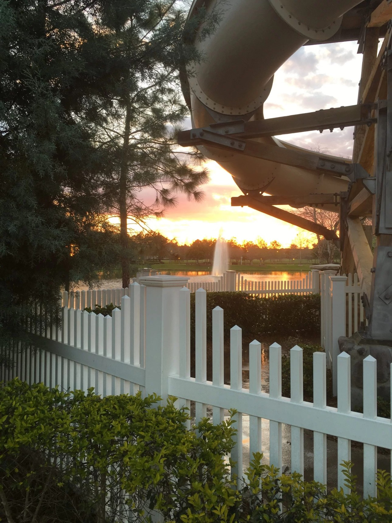 The Paddock pool water slide in front of a sunset next to a pine tree with a fountain and a white picket fence.
