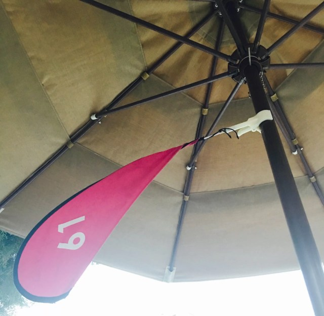 A pool umbrella with a red flag with the number 61 at Paddock Grill.