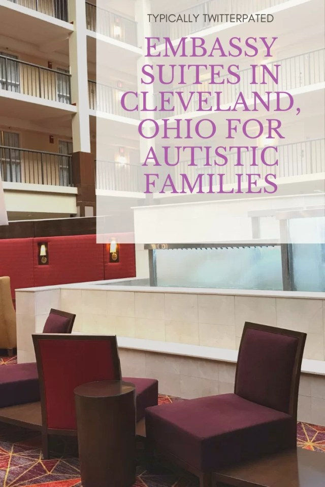 Photo of two red chairs in front of a fountain inside an atrium with the words 'Typically Twitterpated EMBASSY SUITES BEACHWOOD FOR AUTISTIC FAMILIES'