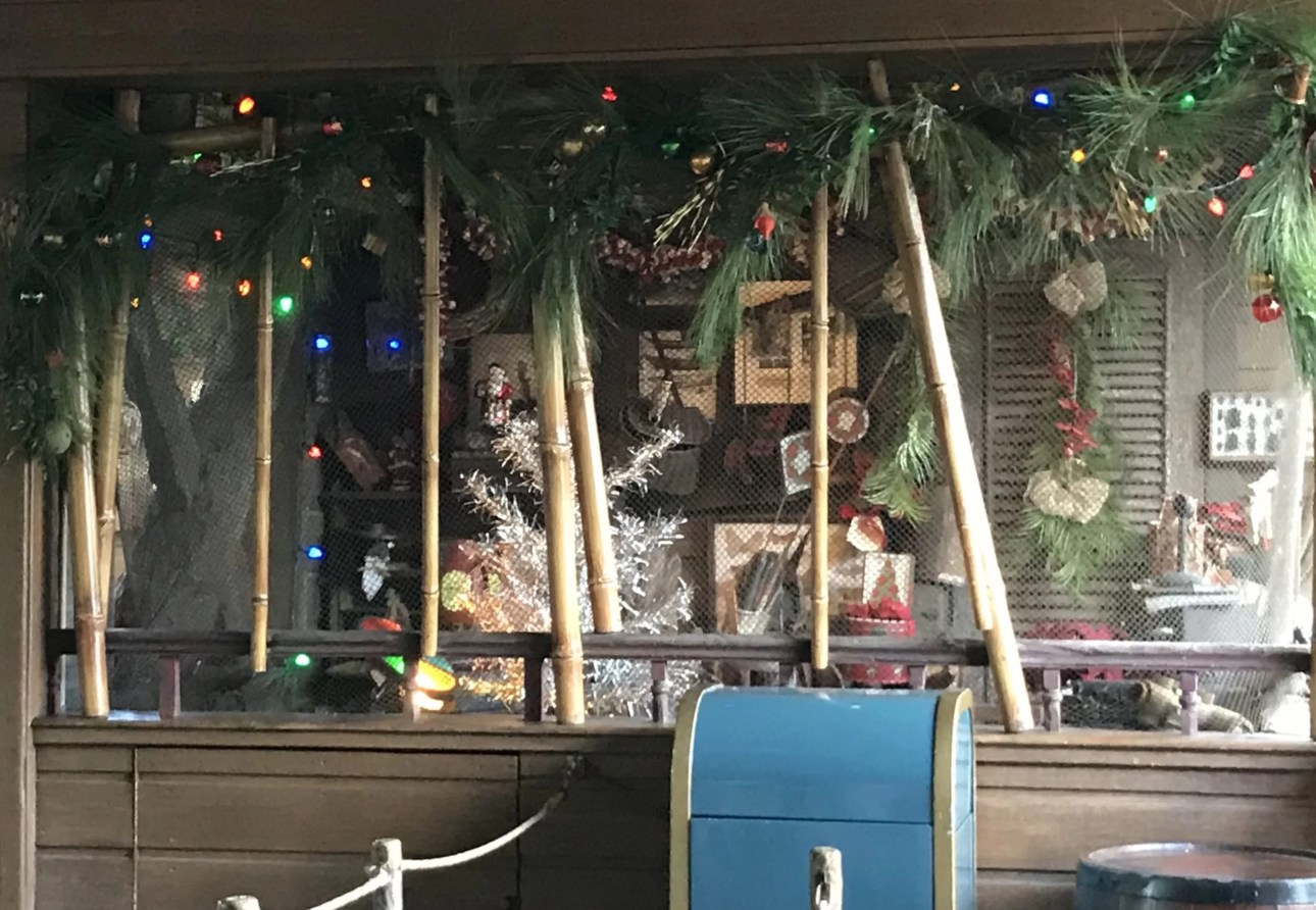 Jingle Cruise lights with evergreen bough and christmas tree in cruise operators
