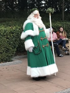 Father Christmas in a green suit with fur and a wreath on his head in the United Kingdom at Epcot World Show case