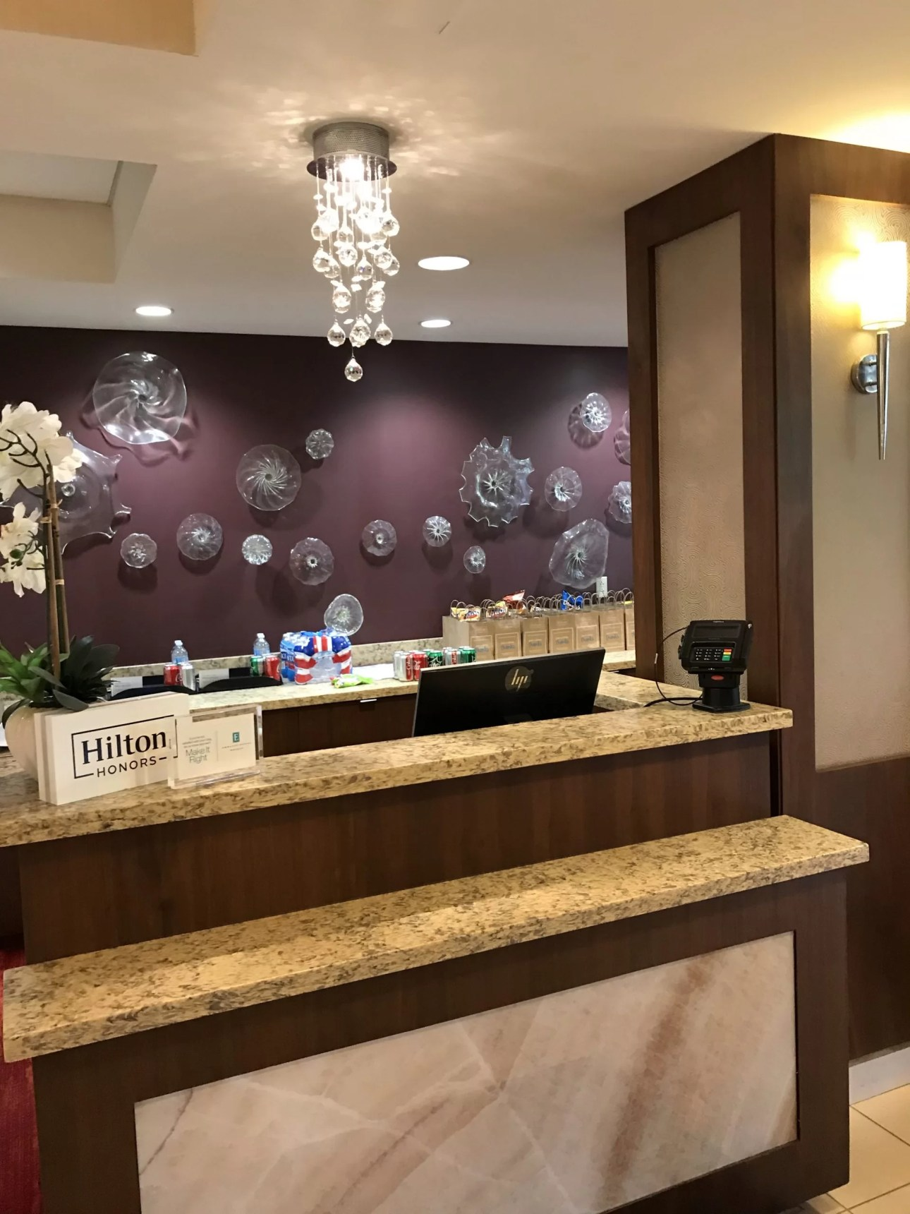 A hotel front desk in front of a purple wall with glass baubles on it and a light fixture with small glass globes hanging from it.  A Hilton placard and white flower on the desk.