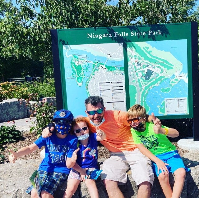 Niagara Falls State Park sign with family giving the thumbs up