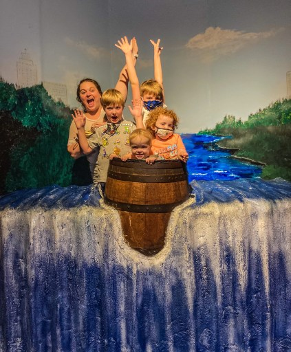 family of five in barrel over faux blue waterfall