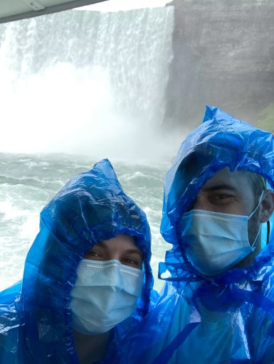 A man and woman in blue hooded ponchos with face masks in front of the American Falls on the Maid of the Mist