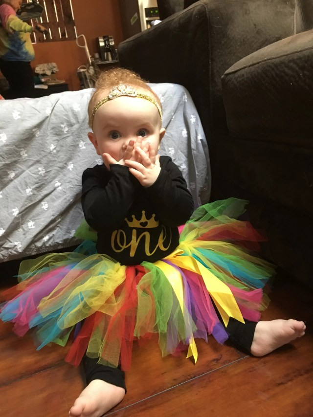 first birthday baby girl in rainbow tutu and gold tiara