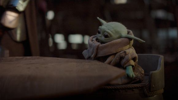 The baby Yoda sitting at a table looking cute as can be.