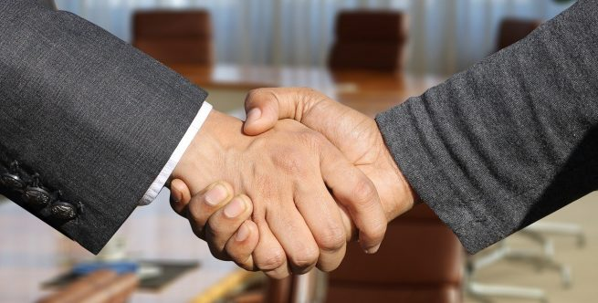 A business owner and a clearance agent shaking hands