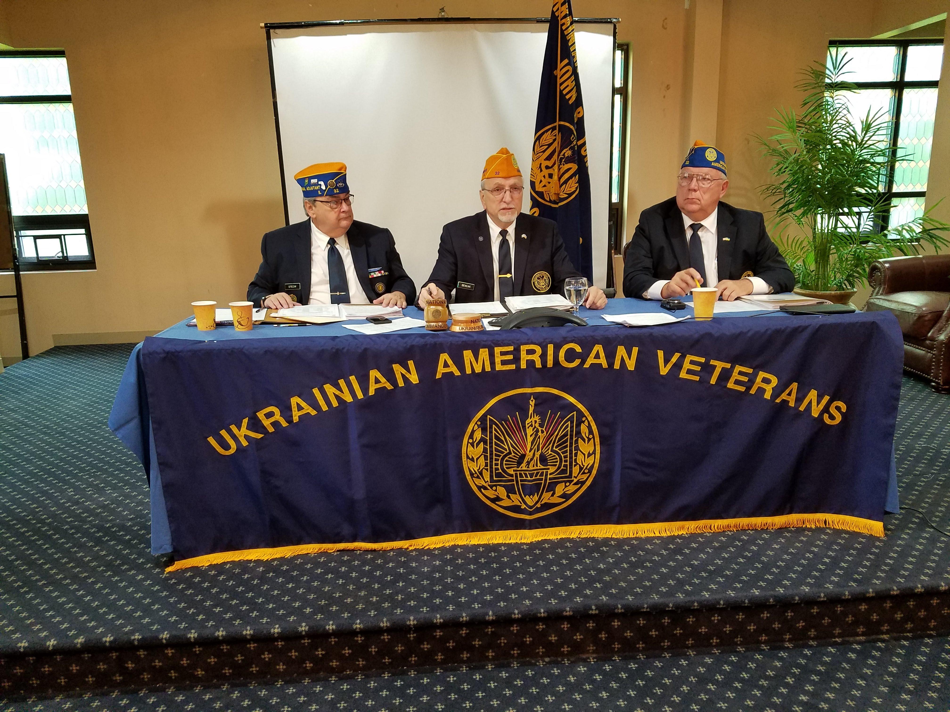 Ukrainian American Veterans (UAV) officers seated behind UAV banner