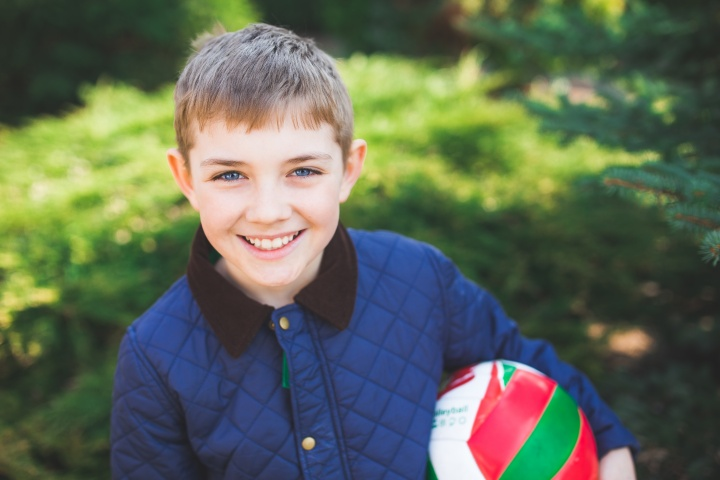 A young boy holding a ball and smiling.