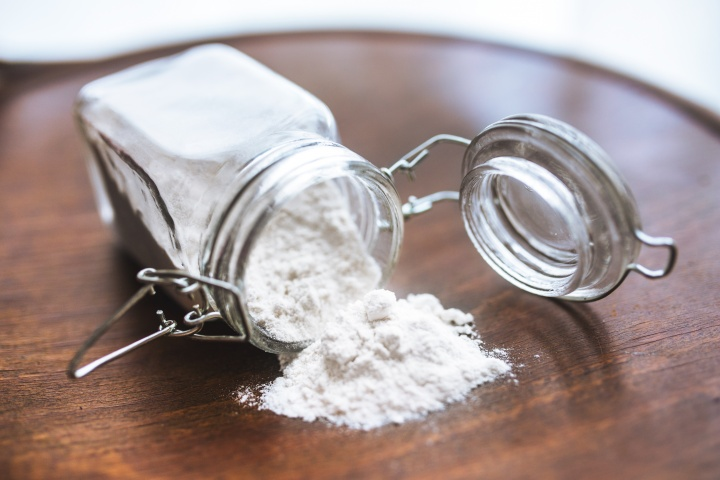 A glass jar of flour on its side with flour spilled out.