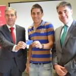 Amador Fraile (izqda.) y Tomós López (dcha.) entregan la nueva tarjeta inteligente a un alumno