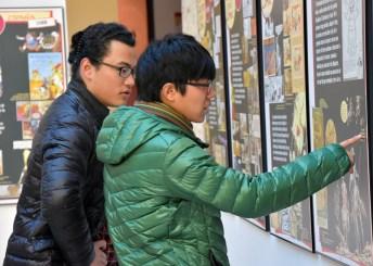 Dos estudiantes internacionales contemplan la muestra en el vestíbulo de Humanidades