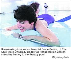 Rosemarie Rossetti grimaces as her leg is stretched by therapist Diane Brown