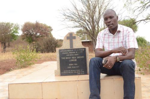 Frank Obonyo, author of story, at marker recognizing the late archbishop (UCU Photo)