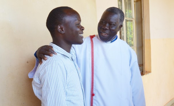 Rev. Canon Odora interacts with a member of the congregation outside St. Phillip's Cathedral in Gulu shortly after a service on January 1, 2019. (UCU Partners photo)