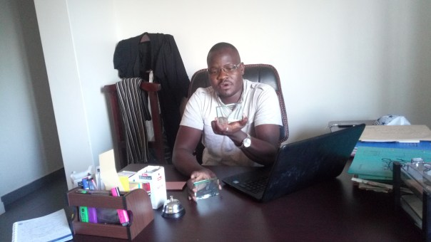 Conrad Oroya displays some accolades at his office in Gulu