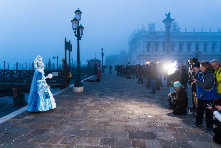 Photographers and masks near St. Mark's Square in the early morning hours during the Carnival of Venice