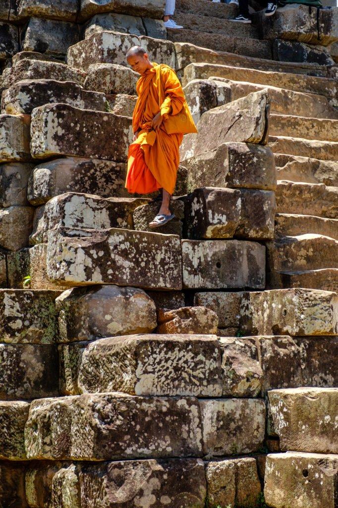 Buddhist monk climbing down stairs at Ta