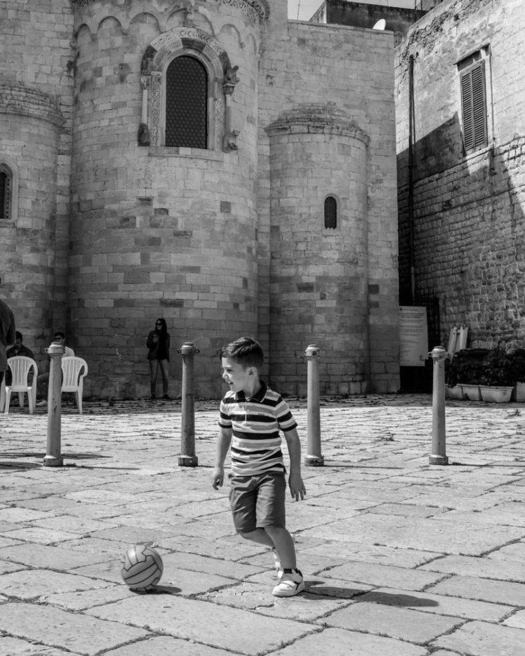 Kid playing football. Trani, Italy