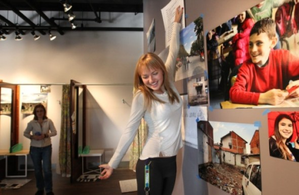 American High School student Tess Davey hangs artwork from a recent trip to Kosovo on the walls of lululemon. (Phil Masturzo/Akron Beacon Journal)