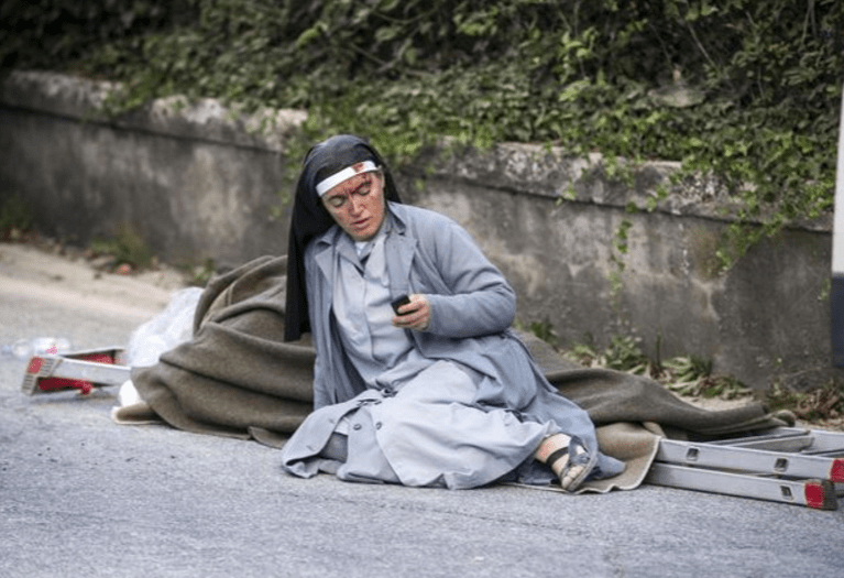 Sister Mariana, from Albania, checks her mobile phone as she lies near a victim laid on a ladder following an earthquake in Amatrice, Italy on Wednesday, Aug. 24, 2016.