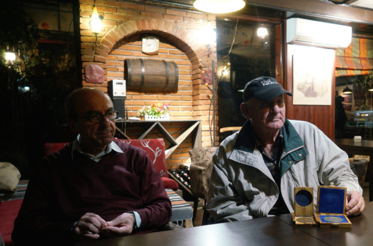 Rexhep Hoxha, left, and Fatos Qoqja in a bar in Tirania, Albania, Nov. 8, 2017. Qoqja is pictured with a medal that his father received for saving Jews during the Holocaust. (Cnaan Liphshiz)