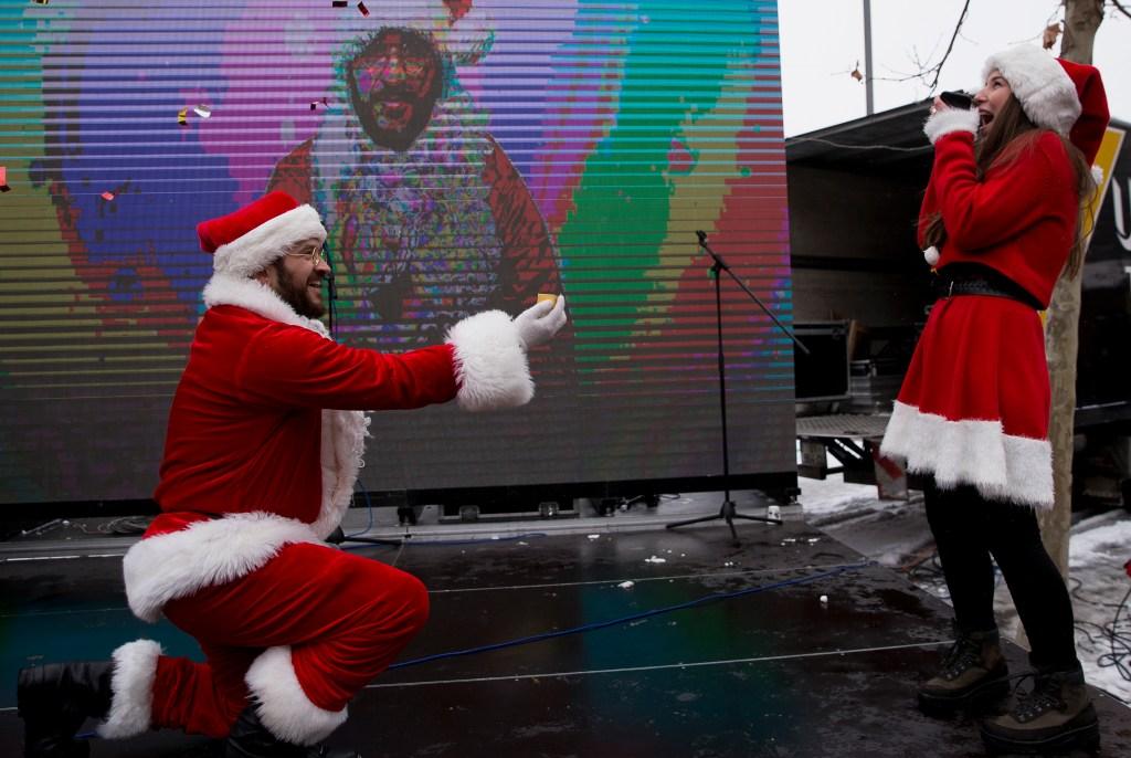 Jusuf Islami proposes to his partner Hana during the 3rd Santa Claus run in Kosovo's capital, Pristina, on Sunday, Dec. 16, 2018. (AP Photo/Visar Kryeziu)
