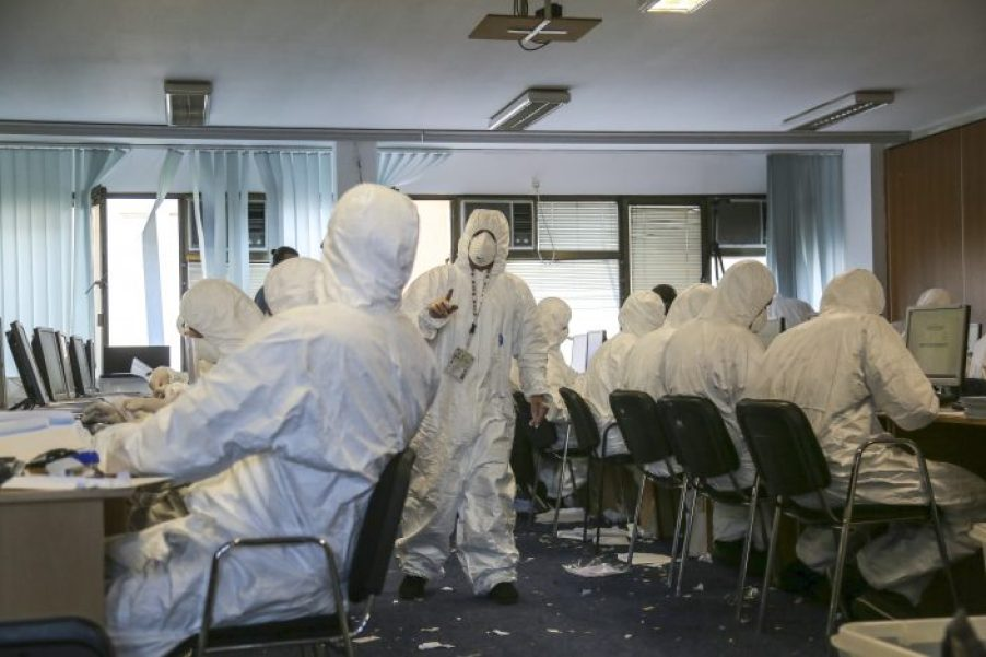 Central Election Commission officials are dressed in white disposable overalls and wearing face masks as they count votes arrived from Serbia in Kosovo capital Pristina on Wednesday, Oct.23, 2019. Vote counting has been suspended in Kosovo after several Central Election Commission officials reported health problems including allergic reactions and skin problems after opening ballot boxes from Serbia, authorities in Kosovo have said.(AP PhotoVisar Kryeziu)