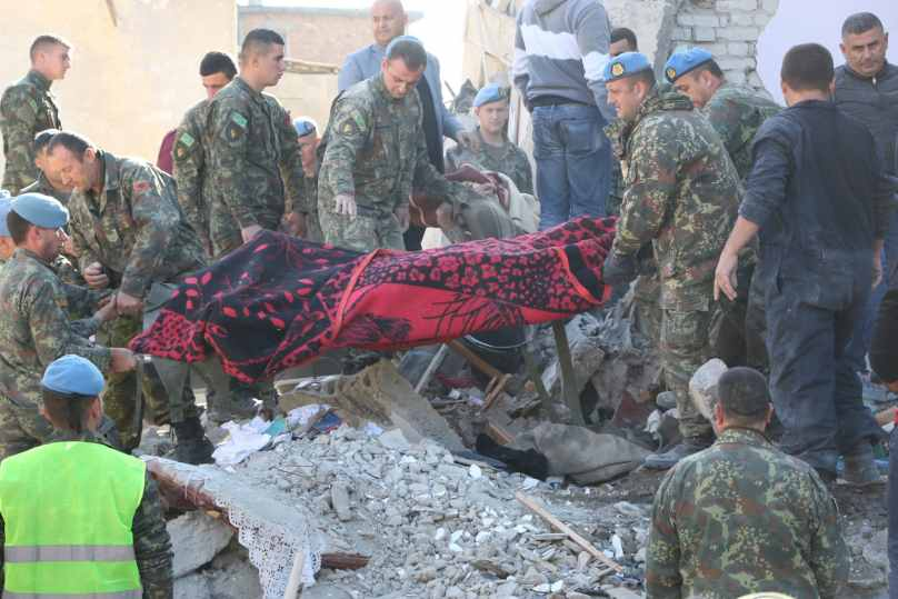 Soldiers carry a dead body pulled out from earthquake debris in Durres. Credit: Anadolu Agency/Getty