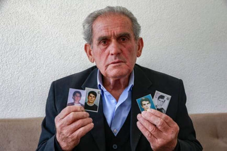 In this Monday, May 4, 2020 photo, Halil Hasani displays four photos of his missing sons from right to left Fadil, 32, Gazmend , 24, Armend, 20, and Hasan, 15, taken by Serb forces during the Kosovo war over two decades ago, as he sits in the porch of his house in the village of Qabra. Hasani is convinced his four sons are alive and imprisoned somewhere in Serbia more than two decades after police and paramilitary forces took them from a village in Kosovo. At the time, an armed uprising by ethnic Albanian separatists had led to a bloody Serb crackdown, an international crisis and a NATO bombing campaign in Kosovo, then a Serbian province. (AP Photo/Visar Kryeziu)