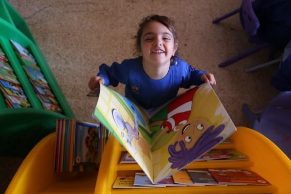 A child sponsored by UK Care for Children reads a book
