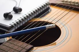 notebook and headset on top of an acoustic guitar