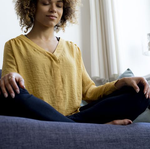 young-woman-sitting-on-couch-at-home-meditating-royalty-free-image-1584121929