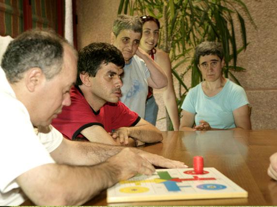Jon, Alberto, Reyes y Lidia jugando una partida de parchís, una actividad lúdica en un espacio común con otros compañeros.