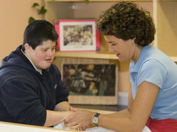 Josefa en el área de estimulación sensorial recibiendo un masaje en las manos por parte de su cuidadora Carmen.