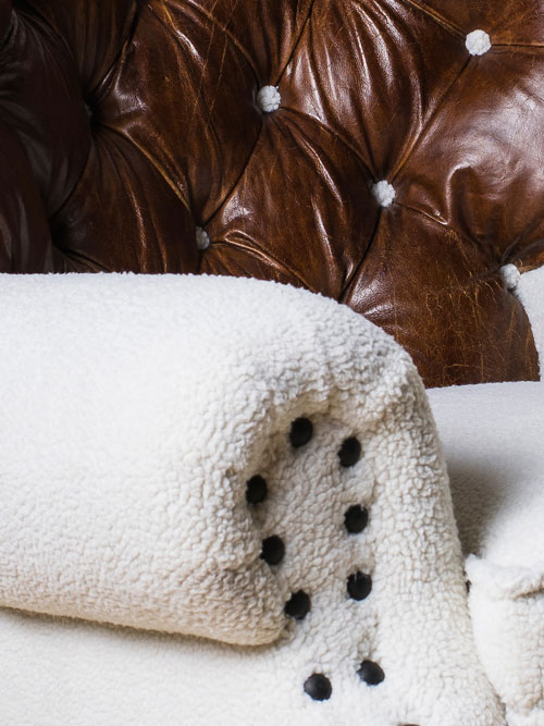 Detail of Papa Bear chair by Ulloo42 with faux shearling, distressed leather and painted metal nail heads