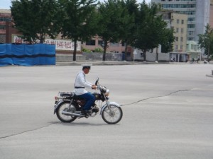 A North Korean policeman is a human traffic light, directing few cars between occasional lone circling of the intersection.