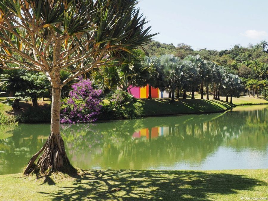"""Reflections in a pond at Inhotim: tropical vegetation, and the colourful walls of the """"Magic Square"""" by Hélio Oiticica in the background."""