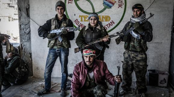 Des combatants kurdes de la milice YPG posent après avoir repris le centre culturel de Kobané, en Syrie, des mains du groupe Etat islamique, le 22 décembre 2014.