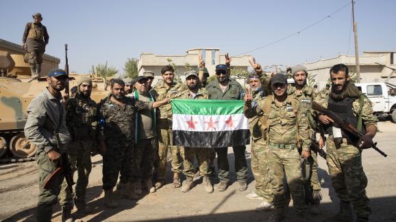 Des membres de l\'Armée nationale syrienne posent avec un drapeau syrien en arrivant à Tell Abyad, en Syrie, dans le cadre de l\'offensive menée par la Turquie, le 10 octobre 2019.