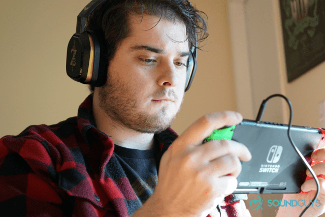 A man plays a Nintendo Switch while using the Legend of Zelda Breath of The Wild Astro A10 gaming headset.